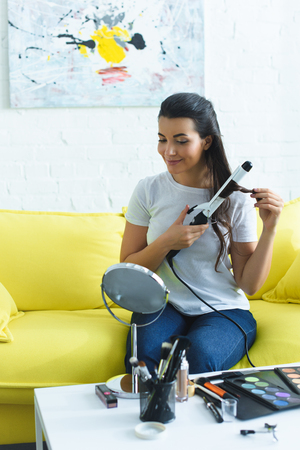 portrait of young smiling woman with curling iron doing hairstyle at home