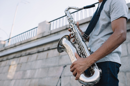 Cropped view of african american man playing saxophone performing on sunny city street