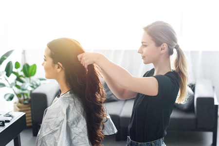 side view of hairstylist doing hairstyle to young woman on chair Stockfoto