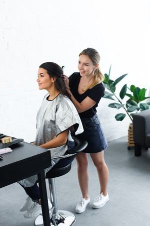 side view of smiling hairstylist with comb doing hairstyle for young woman