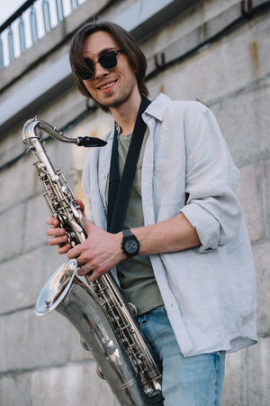 Smiling hipster man in sunglasses holding saxophone in urban environment