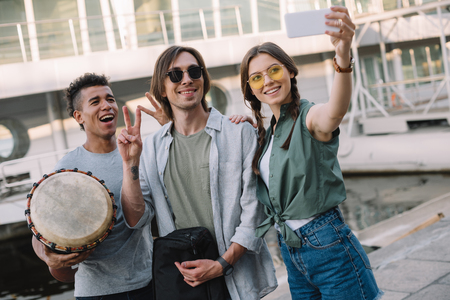 Team of young musicians with instruments taking selfie in urban environment