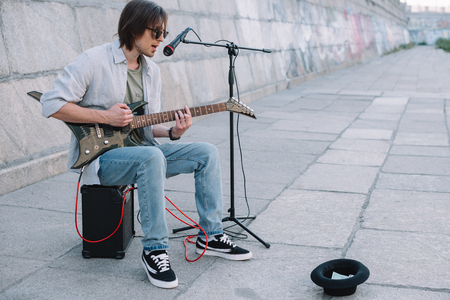 Young happy busker playing guitar and singing at city street Foto de archivo