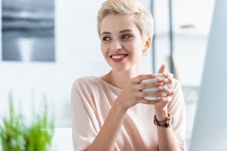 portret van vrouw met kopje koffie en wegkijken Stockfoto