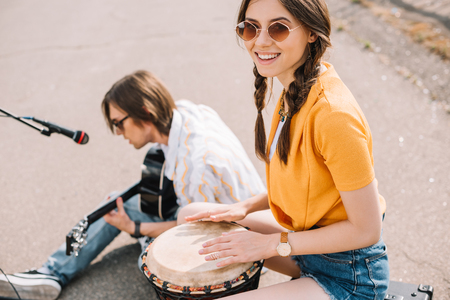 Couple of young street musicians smiling and performing in urban environment