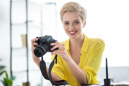 portrait of female photographer holding camera at table in photostudio