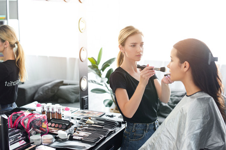 side view of focused makeup artist applying powder on womans face with brush Zdjęcie Seryjne