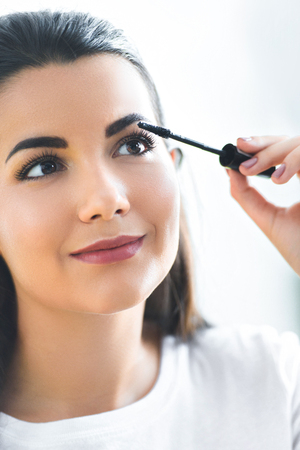 portrait of attractive young woman applying black mascara on eyelashes