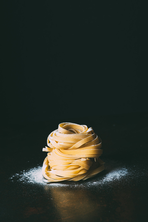 close up view of raw tagliatelle pasta and flour on table on black background