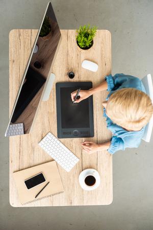 Vue de dessus du pigiste travaillant sur tablette graphique à table avec tasse de café, smartphone et ordinateur au bureau à domicile Banque d'images