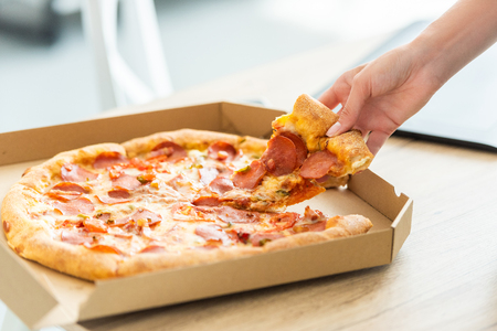 cropped image of woman taking pizza slice from box at table