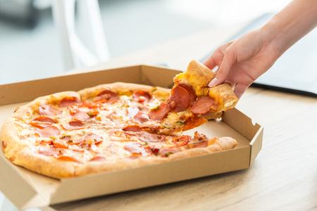 Imagen recortada de una mujer tomando una rebanada de pizza del cuadro en la mesa