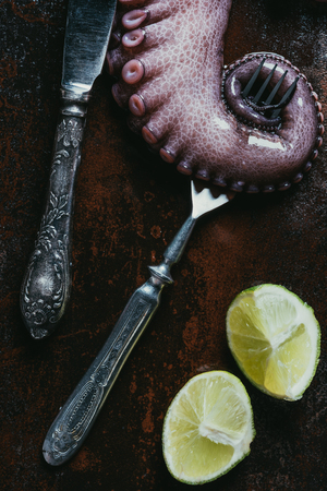 top view of big octopus tentacle with fork, knife and limes on rusty metal surface