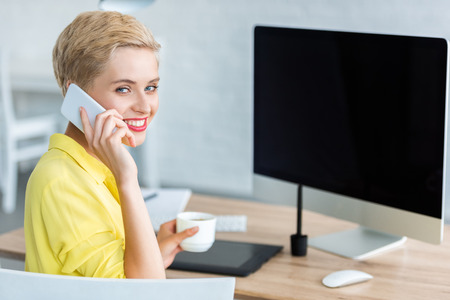 smiling female freelancer drinking coffee and talking on smartphone at home
