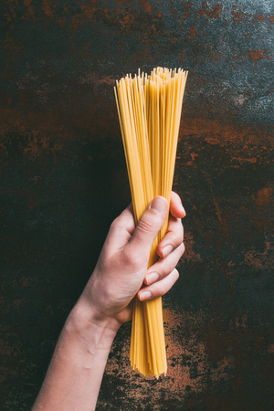 cropped image of man holding raw spaghetti over rustic metal tabletop