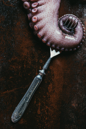 top view of big octopus tentacle with fork on rusty metal surface