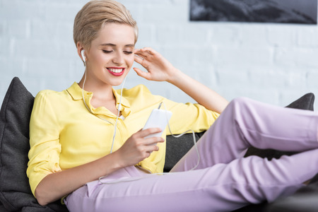 happy young woman listening music in earphones with smartphone on sofa at home Stock Photo