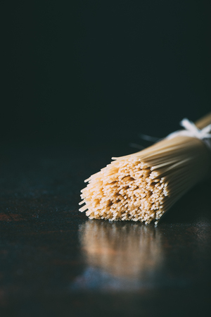 closeup view of spaghetti wrapped by ribbon on black background