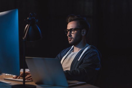 young programmer in eyeglasses working with desktop computer and laptop at night