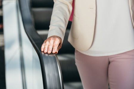 cropped image of woman on escalator in shopping mall
