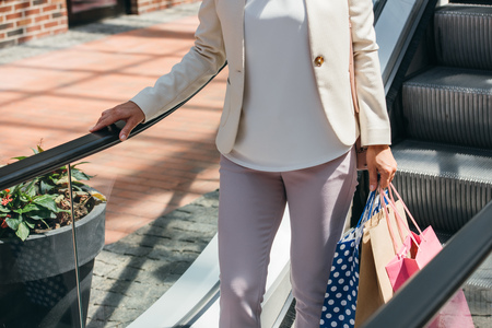 cropped image of woman on moving staircase with shopping bags in mall