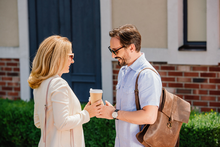 side view of couple standing with disposable coffee cups on street Stock Photo