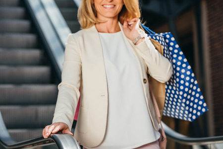 cropped image of smiling woman standing on escalator with shopping bags in mall Banco de Imagens