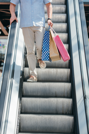 cropped image of man walking on escalator with shopping nags Banco de Imagens