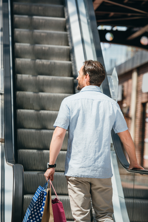 back view of man standing on escalator with shopping bags in mall Stock fotó