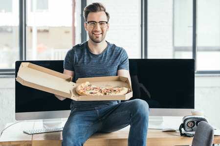 handsome young programmer in eyeglasses holding pizza and smiling at camera