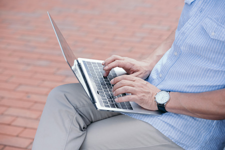 cropped image of man sitting on bench with laptop Stock Photo