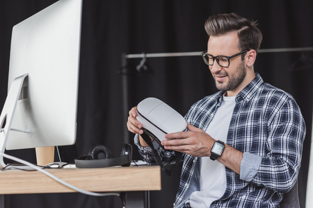 smiling young man in eyeglasses holding virtual reality headset at workplace Stok Fotoğraf