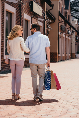 back view of couple walking with shopping bags on street Stock Photo