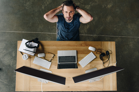 handsome young man with hands behind head looking at camera while sitting at workplace with computers