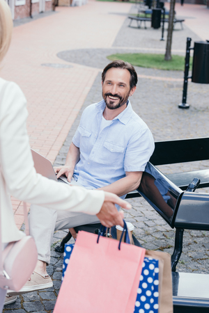 cropped image of couple meeting after shopping on street Stock Photo