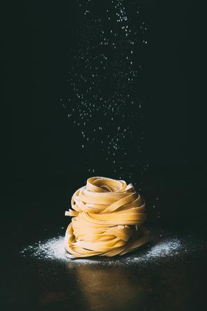 close-up shot van bloem vallen op tagliatelle pasta op zwarte achtergrond Stockfoto