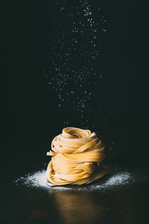 closeup shot of flour falling on tagliatelle pasta on black background