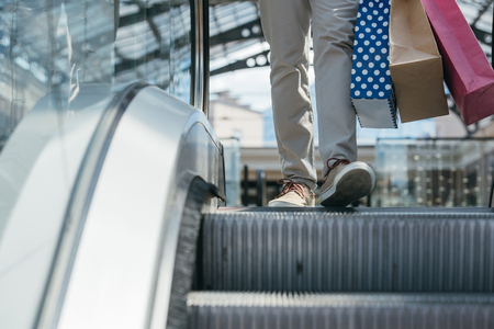 cropped image of man stepping on escalator in shopping mall Banco de Imagens