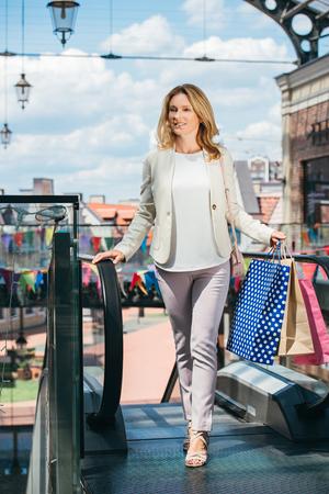beautiful woman walking with shopping bags in mall Banco de Imagens