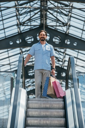 low angle view of handsome man standing on escalator with shopping bags