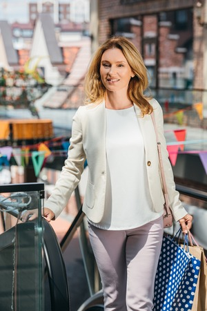 attractive woman walking with shopping bags in mall