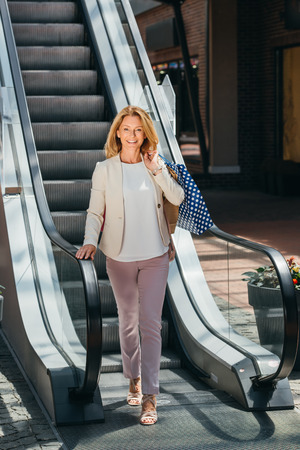 beautiful woman standing near escalator with shopping bags in mall
