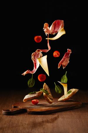 Ingrediënten voor een snack met brood, jamon en groenten die boven houten tafeloppervlak vliegen Stockfoto