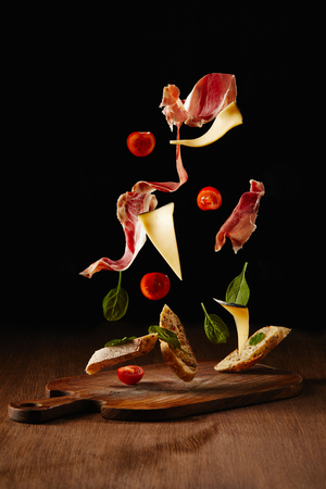Zutaten für einen Snack mit Brot, Marmelade und Gemüse, die über der Holztischoberfläche fliegen Standard-Bild