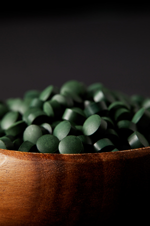 close up view of wooden bowl with pile of spirulina pills isolated on grey background