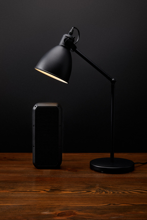 close up view of black audio speaker and lamp on wooden surface on black wall backdrop Stock fotó