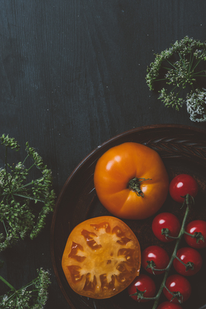 top view of red cherry tomatoes and yellow tomatoes on plate with parsley flowers on wooden background Stok Fotoğraf