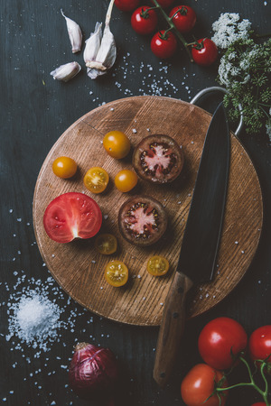 top view of black prince tomatoes and yellow cherry tomatoes on cutting board with knife, garlic and salt Stock fotó