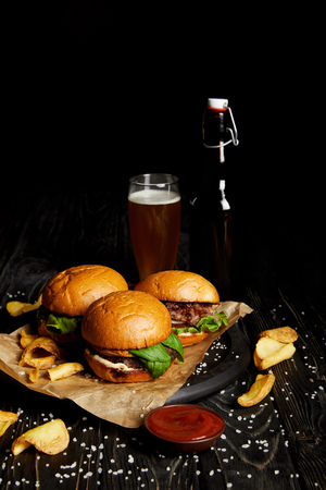 Tempting fast food hamburgers and french fries on table with beer in bottle and glass
