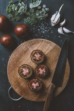top view of black prince tomatoes on cutting board with knife, garlic, salt and flowers